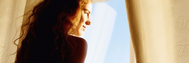 young woman smiling, looking out window