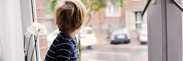 young boy looking out window