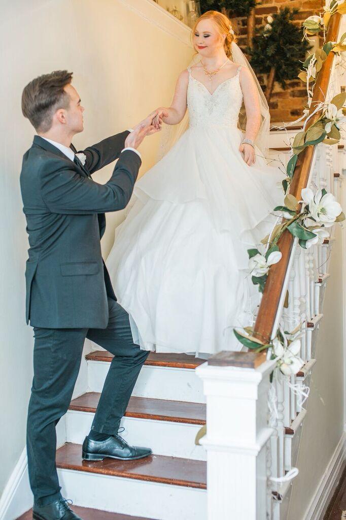 groom escorting madeline stuart down stairs