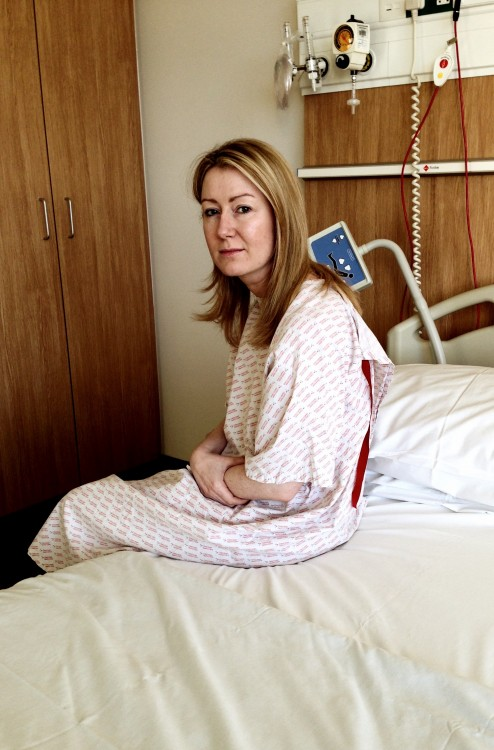 woman sitting on hospital bed wearing hospital gown