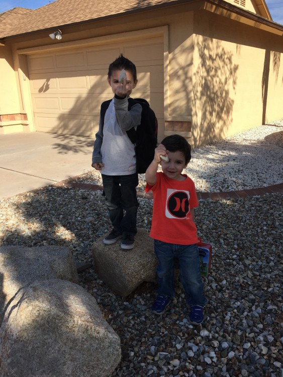 two boys holding up rocks in driveway of house