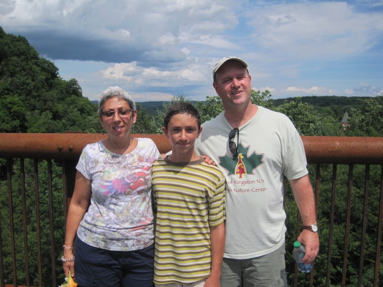 husband, wife and son in front of mountains