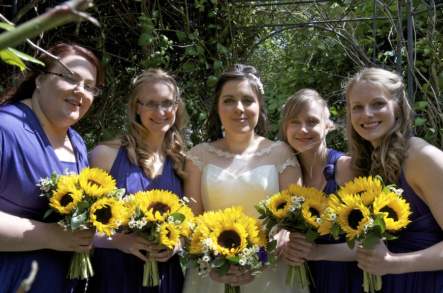 claire with bridesmaids holding sunflowers