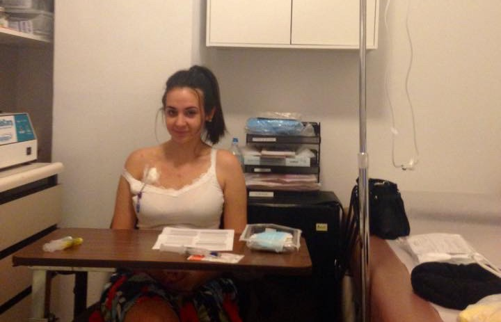 young woman sitting in doctor's office with IV