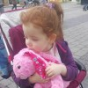 A small girl sits with stuffed animal in stroller