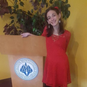 Amy at the Fulton College Podium, smiling and wearing a red dress