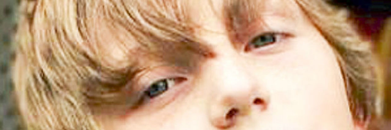Close up photo of a young boy with blonde hair