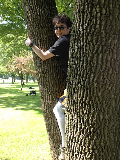 woman climbing tree and smiling