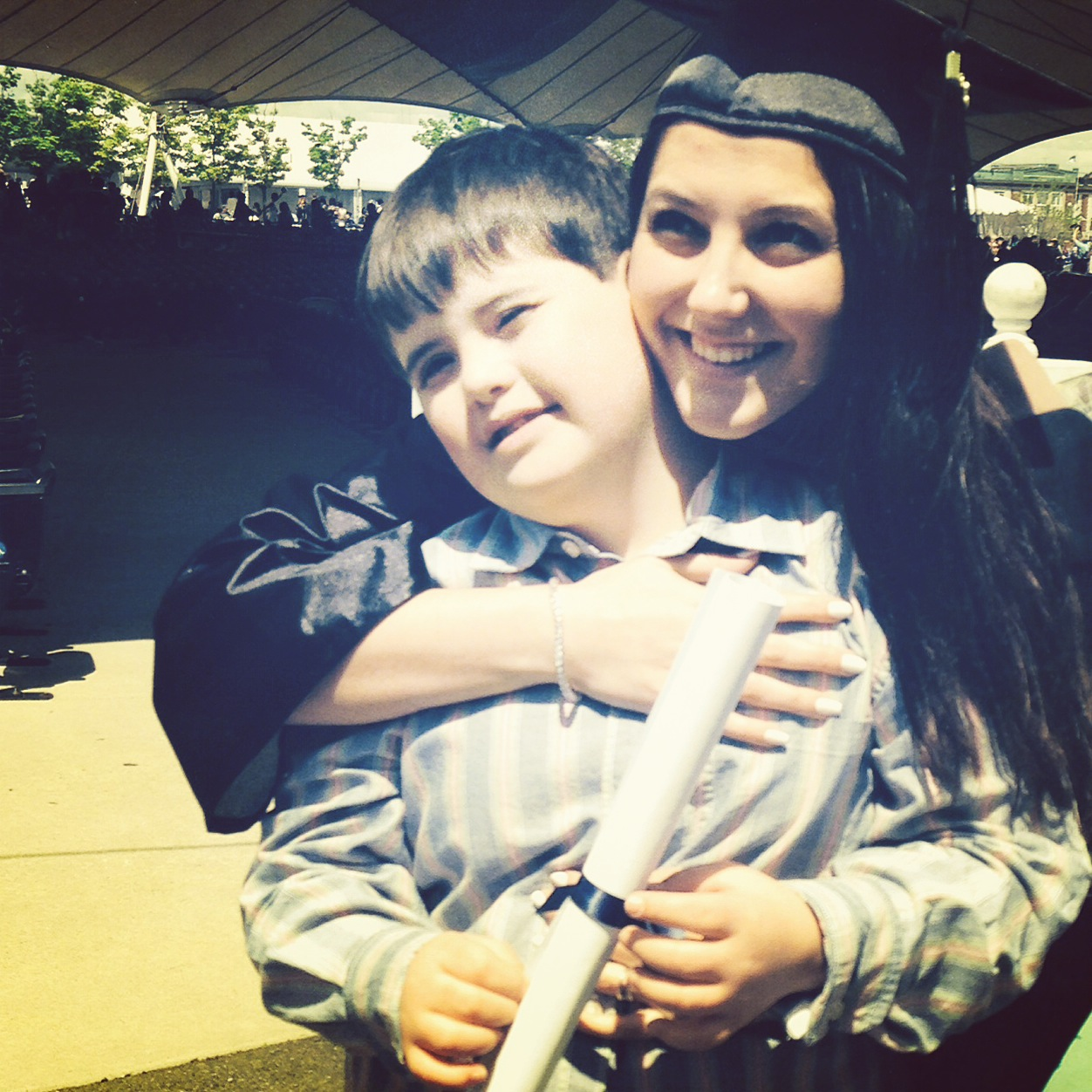 stacey in cap and gown hugging her godson gerry