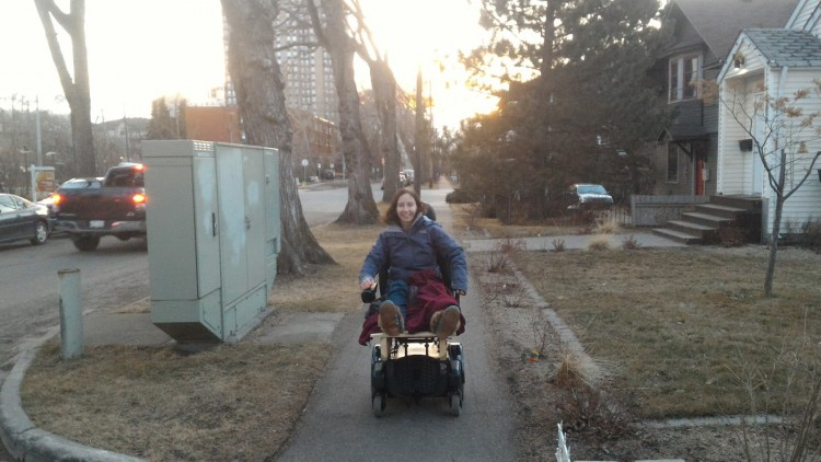 woman in power wheelchair along sidewalk in neighborhood