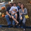 family of parents and two sons sitting on hay bales at halloween