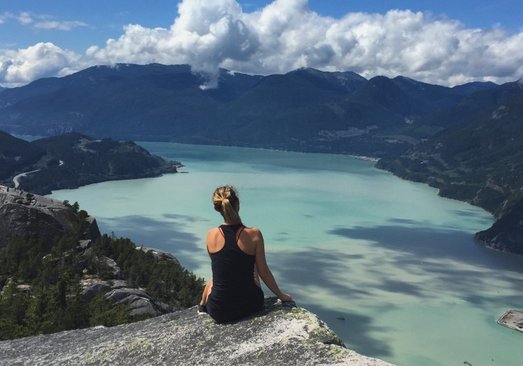 woman sitting on rock looking at mountains and lake