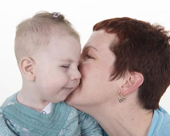 mom kissing baby's cheek