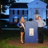 house lit up blue with man and woman standing at blue podium in front