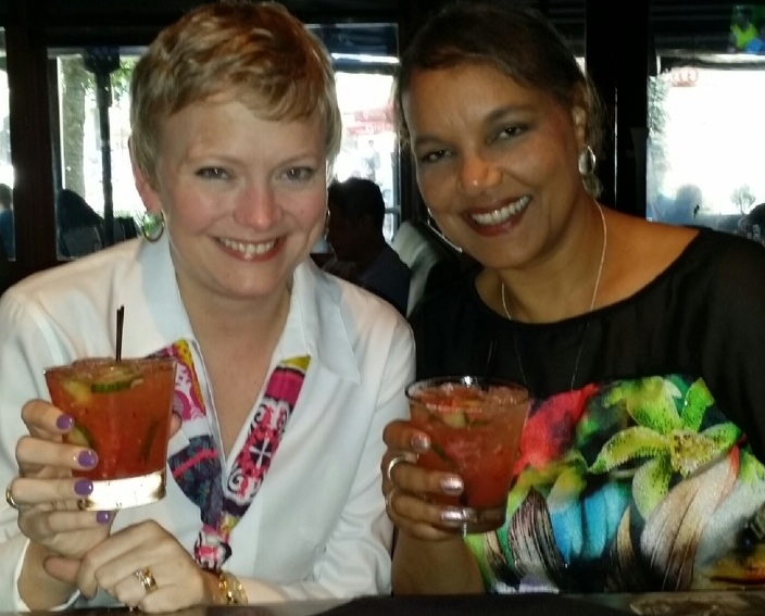 two women drinking tropical cocktails