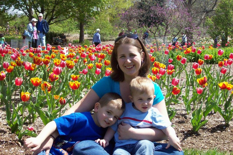 woman and two boys sitting in field of flowers