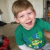 little boy wearing green shirt sitting on floor