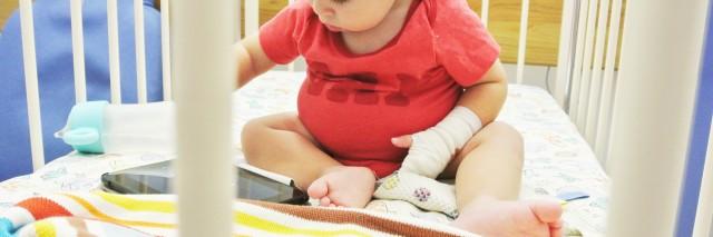 boy playing with iPad in crib