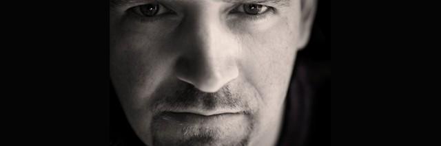 a closeup of a man in dark shadows