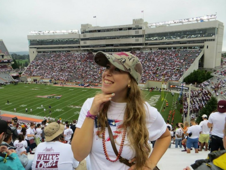 woman smiling with view of football stadium behind