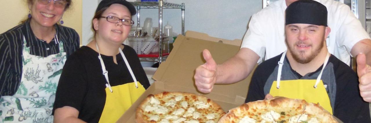 Workers at 'Smiling Hope Pizza' smile for camera as they hold pizzas