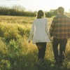 man and woman holding hands walking through field