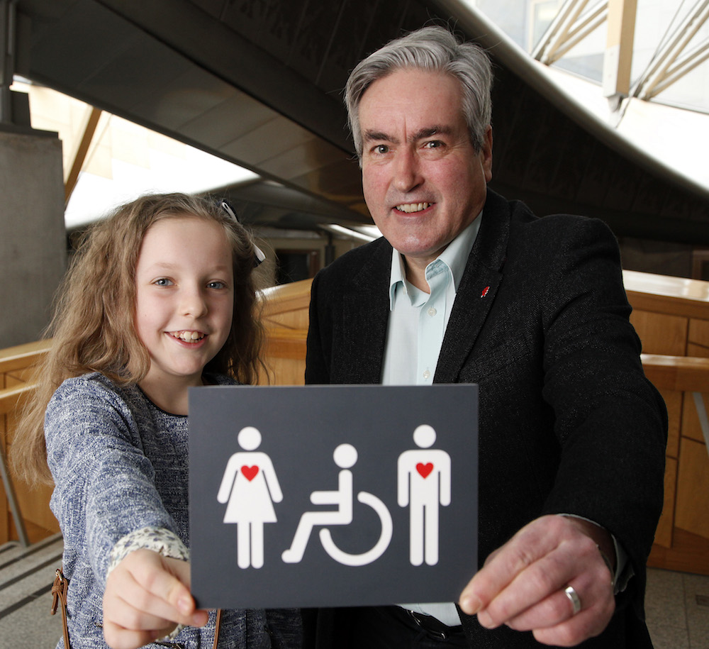 Iain Gray MSP and 10 year old Grace Warnock, a school pupil from Prestonpans in East Lothian, unveil a new disabled toilet signs, designed by Grace.