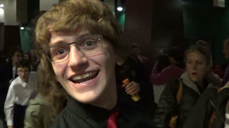 boy with brown hair and glasses smiling at camera