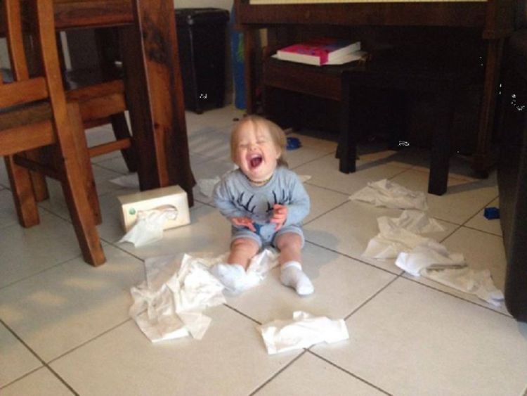 Boy with Down syndrome playing with tissues