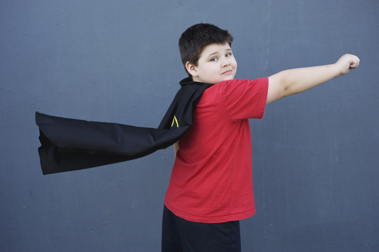 boy in cape poses like superman