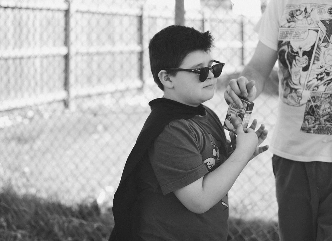 boy wearing cape drinks juice box
