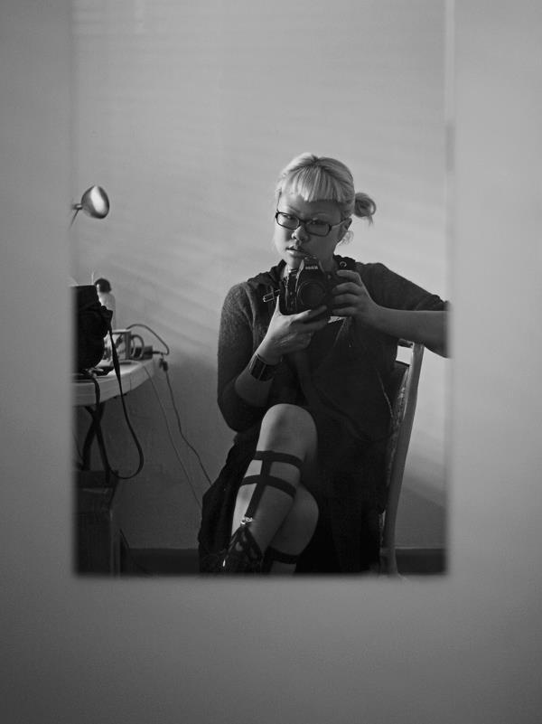 self portrait of photographer sitting facing mirror