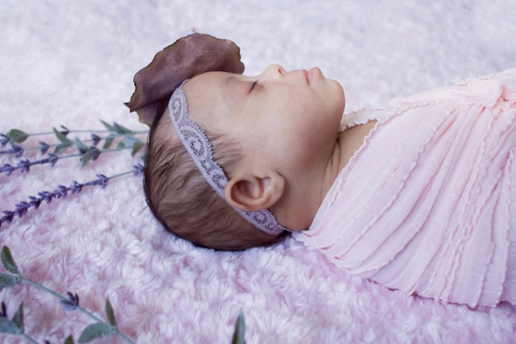 A baby with Down syndrome laying on her back on a pink blanket.