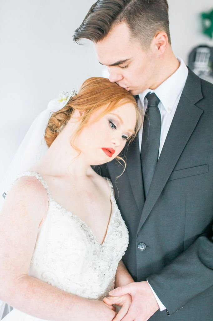groom kissing madeline stuart on the head