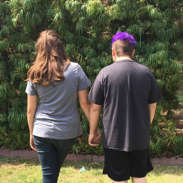 Shawna and her son, standing outside, view from the back. Her son has purple hair.