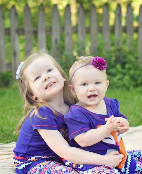 two young sisters wearing matching purple shirts and flower headbands posing together in their yard