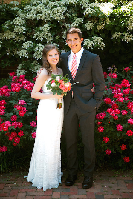 Libby and her husband on their wedding day, standing in front of two rose bushes.