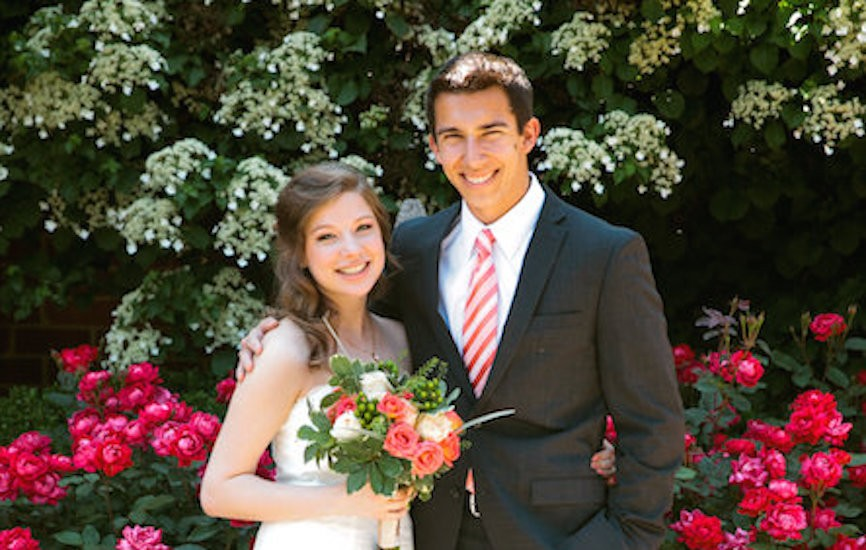 bride and groom posing together in front of flowers
