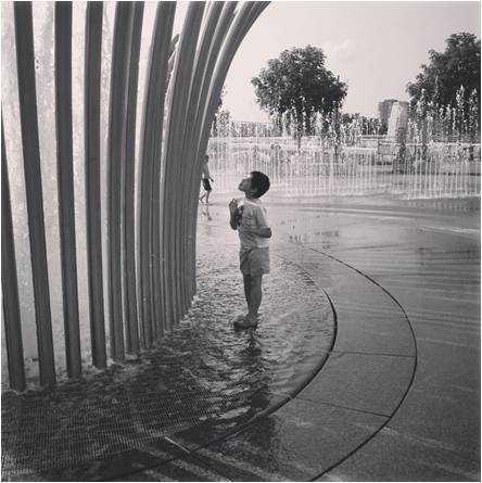 son standing in fountain