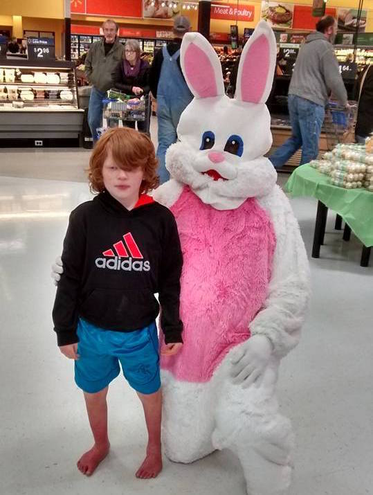 boy with EM standing next to easter bunny in grocery store