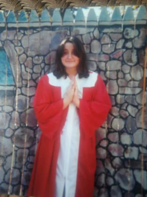 woman in red and white robe holding her hands up in prayer