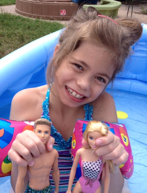 young girl holding up two barbie dolls as she sits in inflatable pool
