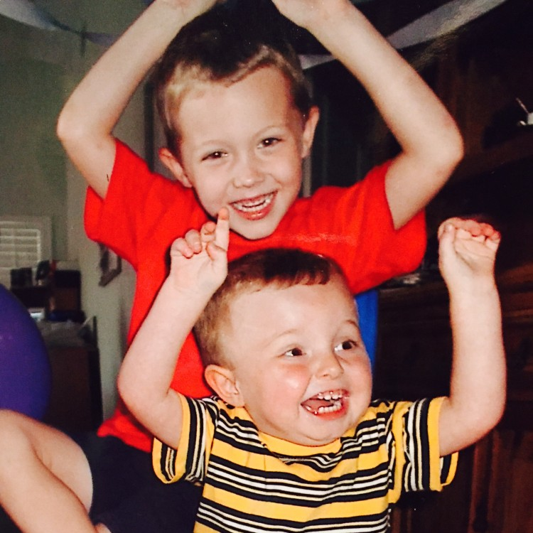 two brothers with their arms raised and smiling