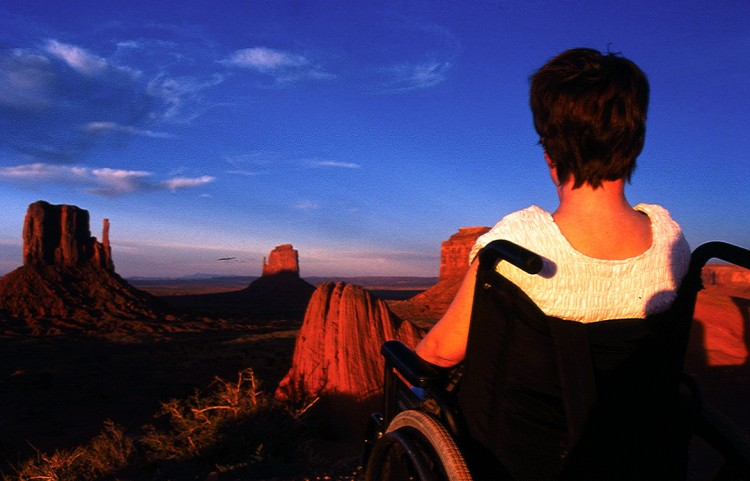 woman in wheelchair looking at sunset over desert