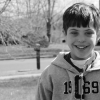 young boy in hoodie in black and white photo