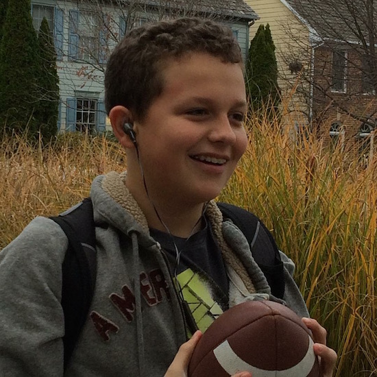 teen boy with headphones and backpack holding a football