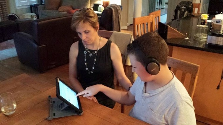 mother sits with her nonverbal son as he writes with the help of a tablet
