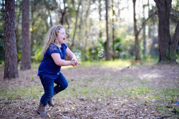 young girl chasing bubbles in the woods