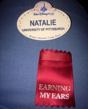 "A close up of Natalie's name tag, and a ribbon that means ""earning my ears"""