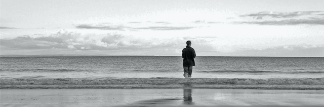 lone man standing next to the ocean